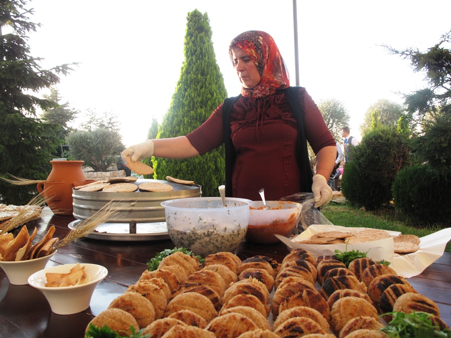 Halima from Aarsal, preparing saj pastries during a catering event