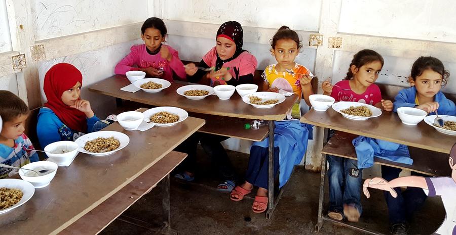Malaak kids enjoying their first meal at school