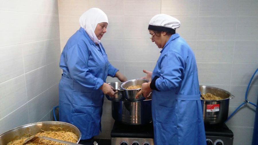 The ladies of Al-Mina CK filling the pots with pasta before delivery