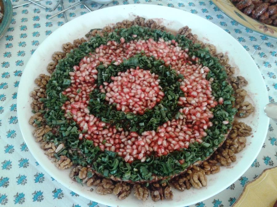 Muhammara decorated with pomegranate seeds, chopped green onions ans walnut